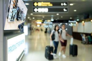 Intelligentes Digital Signage Marketing- und Gesichtserkennungskonzept. Zwei Frauen gehen durch interaktive digitale Werbung mit künstlicher Intelligenz im Einkaufszentrum des Einzelhandels.