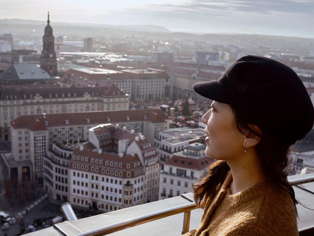 Frau mit Mütze, die über die Dresdner Altstadt schaut