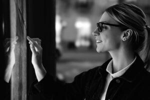 Lächelnde Frau, die an einem großen Bildschirm mit fortschrittlicher Digitaltechnik steht. Junge Frau, die sich mit dem fingerempfindlichen Bildschirm eines interaktiven Kiosks berührt, um Informationen zu finden, während sie abends auf der Straße steht