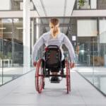 Gelähmte Frau im Rollstuhl unterwegs im behindertengerechten Bürohaus