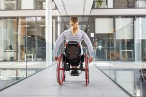 Rollstuhlfahrerin von hinten in Bürogebäude