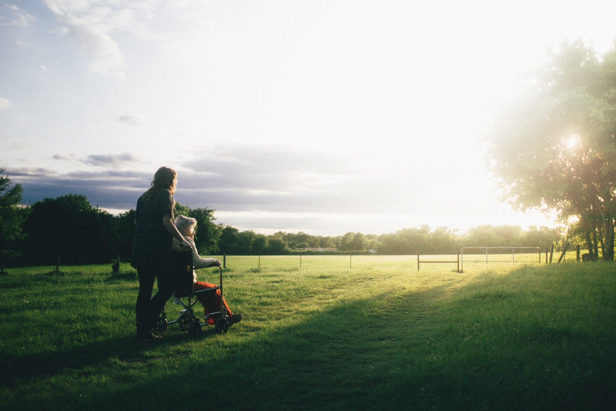 Frau im Rollstuhl schaut sich Sonnenuntergang an