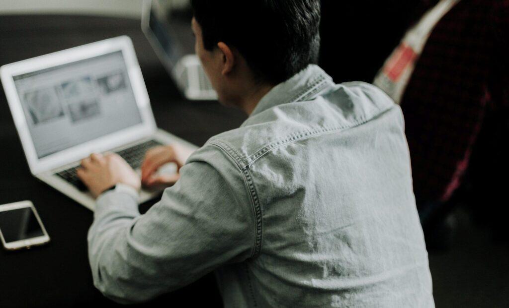 Mann, der am Laptop sitzt