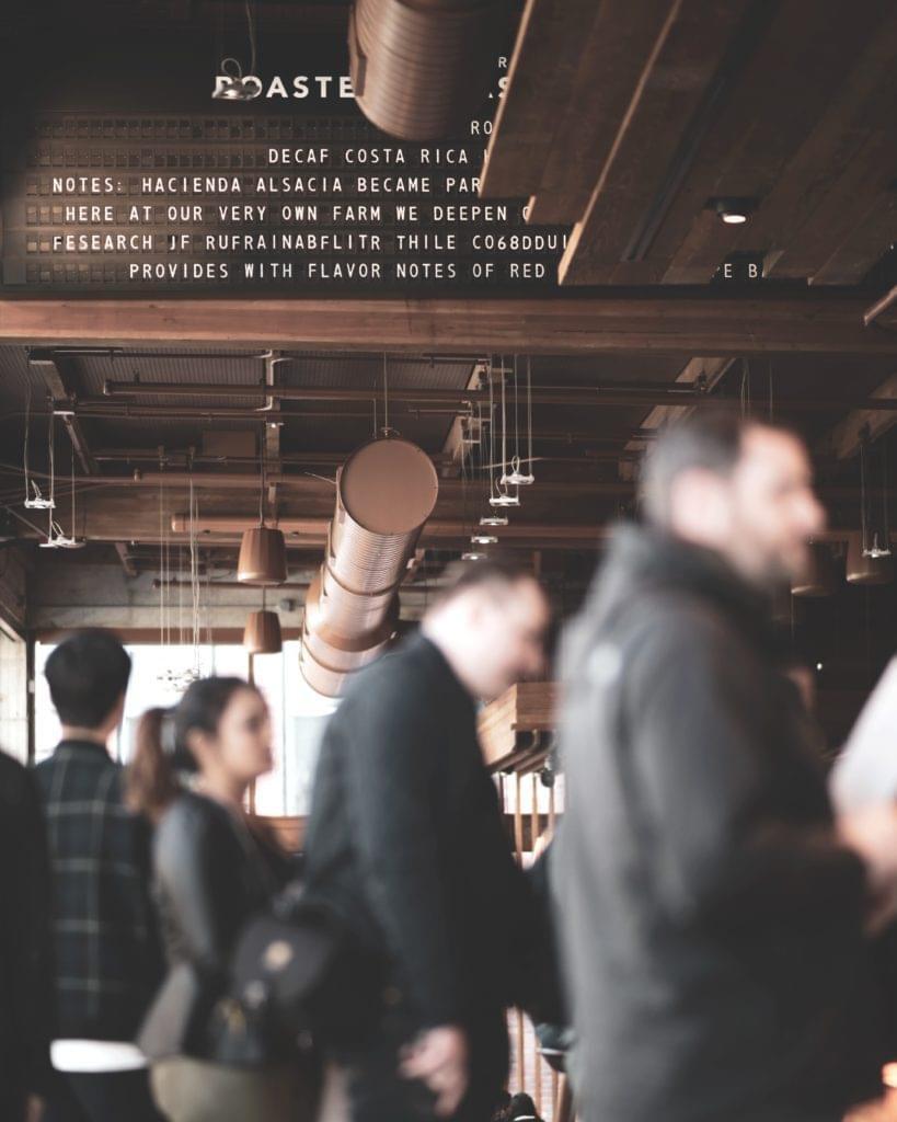 Personen in einem Cafe stehen Schlange