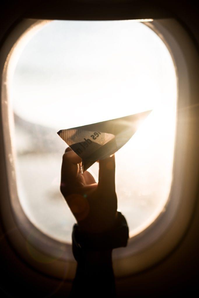Papierflieger in Hand in Flugzeug am Fenster mit Gegenlicht