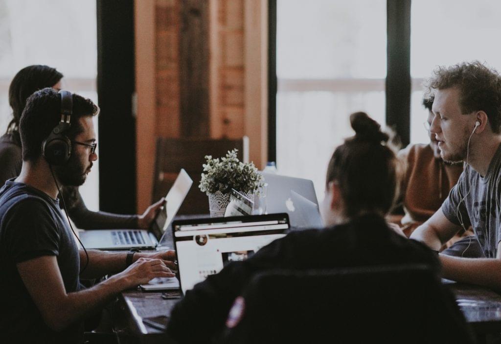 Junge Menschen an Laptops um einen Tisch