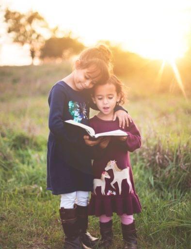 Kinder auf Wiese mit Buch in der Hand