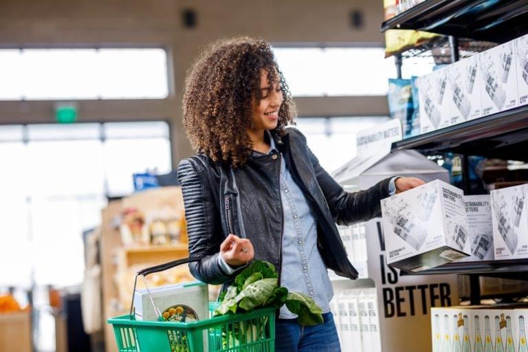 Frau im Supermarkt nimmt Wasser aus einem Regal