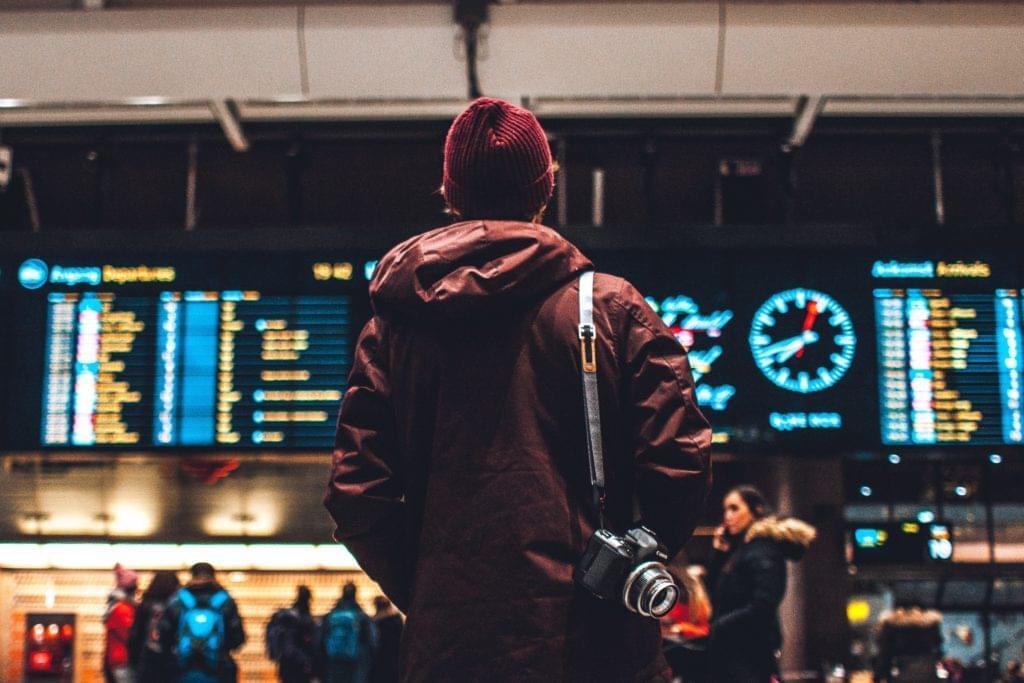Mann am Flughafen ließt Anzeigetafeln