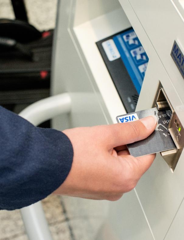 Hand steckt Geldkarte in Aufladeautomat