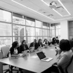 Angestellte, die in einem Konferenzraum an einem großen Tisch sitzen