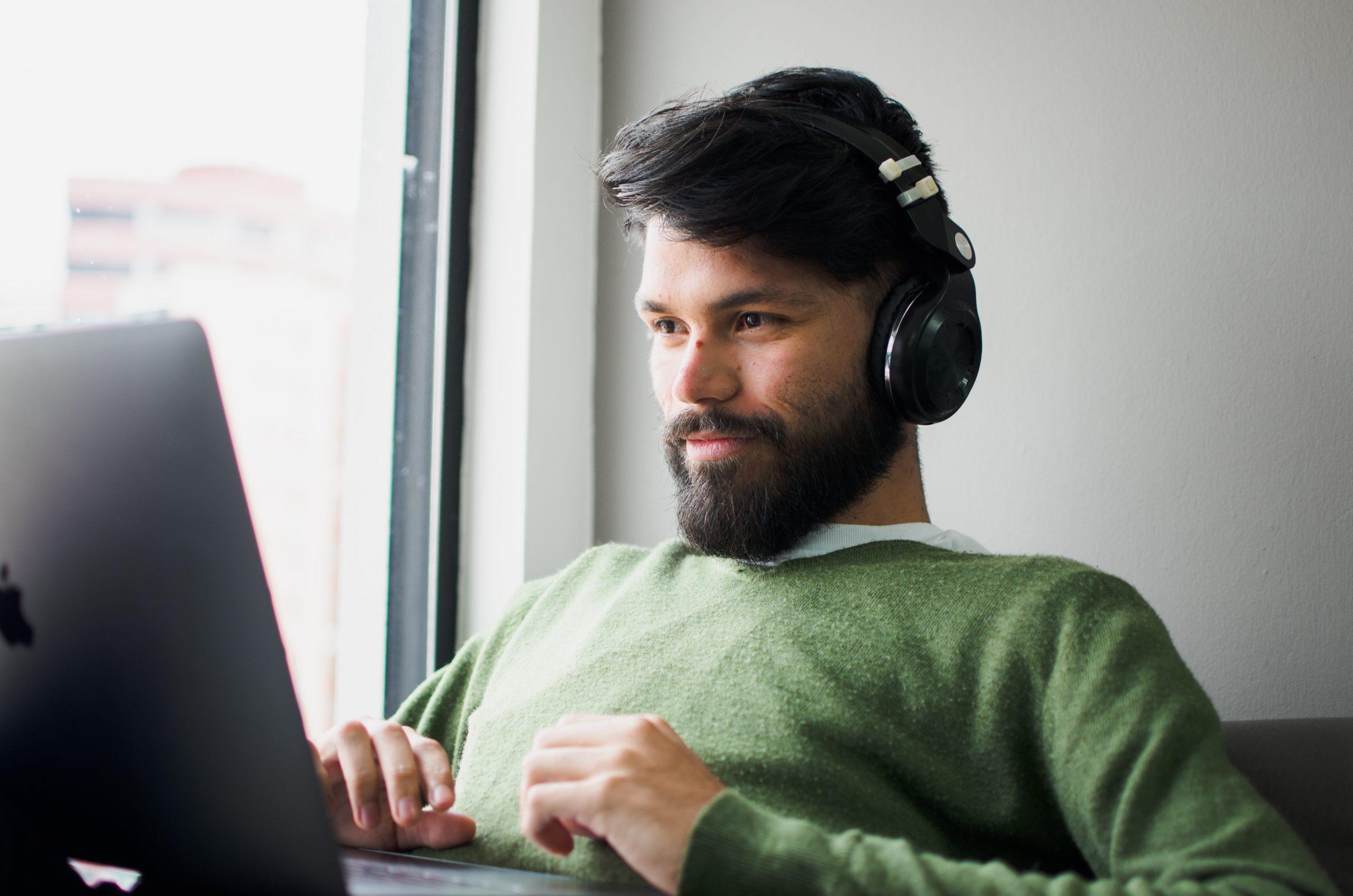 Mann mit Kopfhörern vor seinem Laptop