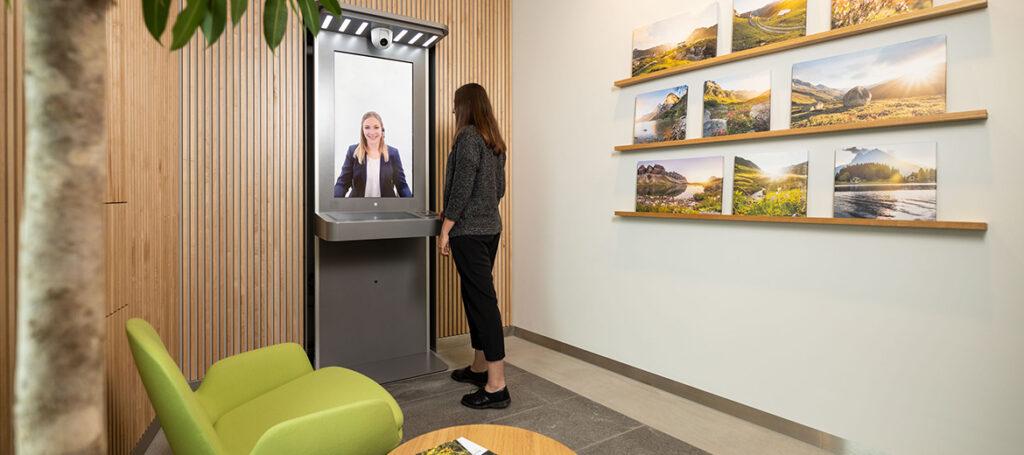Frau steht vor einem Videoserviceterminal. Auf dem Bildschirm ist eine Beraterin zu sehen.
