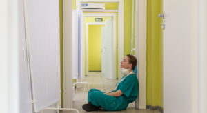 erschöpfte Pflegerin sitzt auf Boden